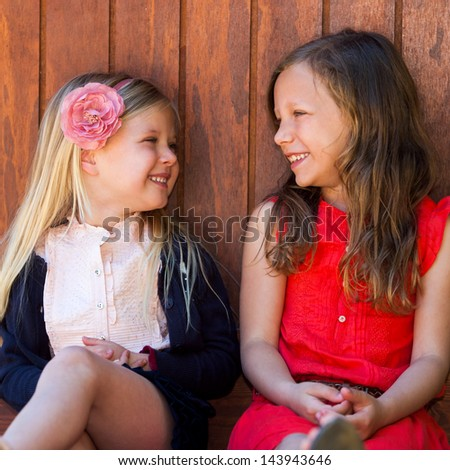 Portrait of two young girls laughing together outdoors.