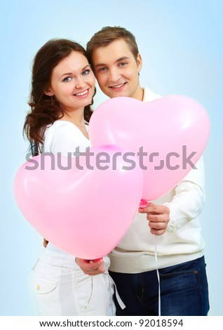 Portrait of two young people holding heart-shaped balloons