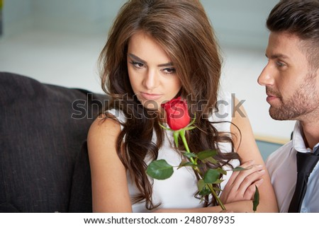 Portrait of two young people looking at each other and holding a rose