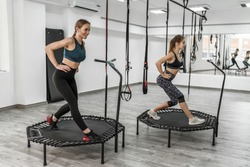Portrait of two young pretty active girls and fitness trainer in sport clothes doing exercises for jump with trampoline during training in gym.