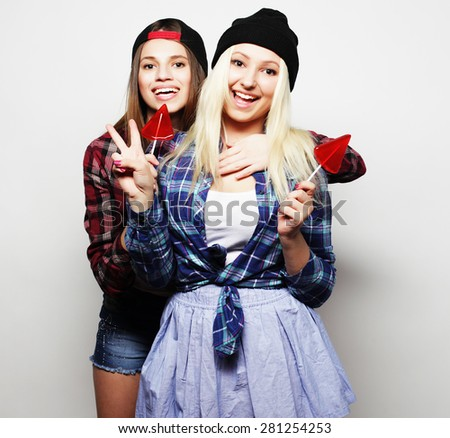 portrait of two young pretty hipster girls wearing hats and sunglasses holding candys. Studio portrait of two cheerful best friends having fun and making funny faces. #281254253