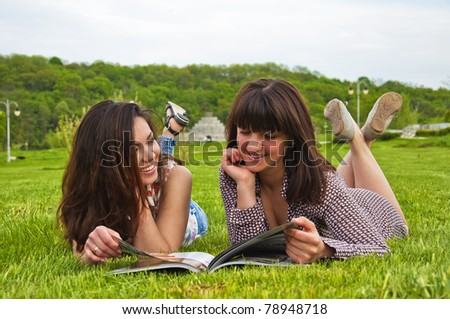 Portrait of two young woman going through the magazine outdoor