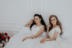 Portrait of two young women in wedding dresses in White Hall