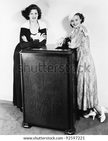 Portrait of two young women leaning against an air conditioner