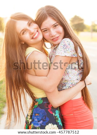 93ad76e061 Portrait of two young women on the street. Walk under the sun. Best friends