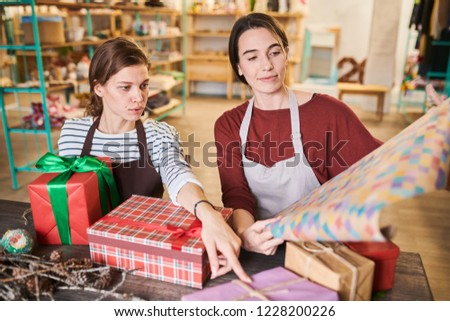 Portrait of two young women packing Christmas presents in store sitting at wooden table