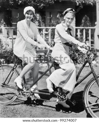 Portrait of two young women sitting on a tandem bicycle Zdjęcia stock ©