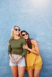 Portrait of two young women standing together over blue background. Stylish young female models looking away and smiling.