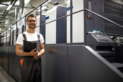 Portrait of typographer standing by modern offset printing machine and checking quality or controlling process of print.