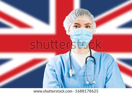 Portrait of UK NHS EMS caucasian hospital frontline ICU GP doctor in PPE Personal Protective Equipment,Great Britain flag background,COVID-19 virus disease crisis,Coronavirus global worldwide pandemic