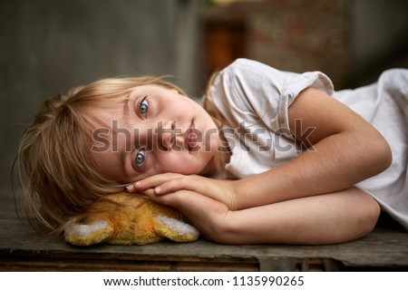 Portrait of unfortunate stray kid lying on the board in the dirty alley, shallow depth of field.