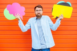 Portrait of unhappy bewildered confused beard business or student man holding varicoloured shapes for dialogs thinking and talking on red background. Problem or difficulty of choosing concept.