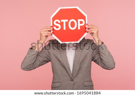 Portrait of unknown business person in suit jacket covering face with Stop symbol, anonymous woman holding red traffic sign stop, warning of danger, restriction and limits. indoor studio shot isolated Foto d'archivio ©