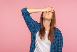 Portrait of unlucky girl in checkered shirt standing with facepalm gesture, feeling regret and sorrow, blaming herself for mistake, frustrated by defeat. indoor studio shot isolated on pink background