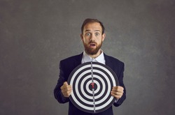 Portrait of unlucky young businessman caught in dangerous trap set up by rivals. Scared man holding dartboard goal becomes target as metaphor of risky business, threat and bad situations at work