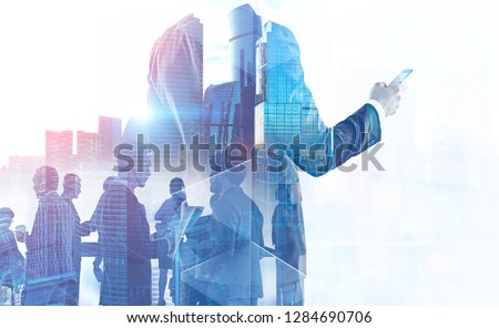Portrait of unrecognizable businessman with cell phone and his business team members over cityscape background. Toned image double exposure