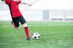 Portrait of unrecognizable teenage boy kicking ball playing football on stadium during practice, copy space