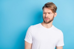 Portrait of unsatisfied man look interested empty space sullen eyebrows lips isolated on blue color background