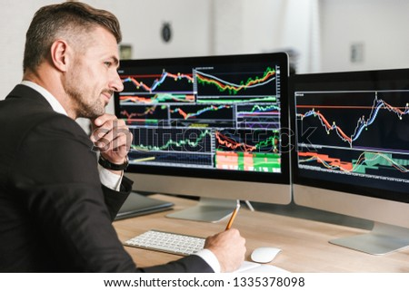 Portrait of unshaved businessman 30s wearing suit working in office and looking on computer with graphics and charts at screen