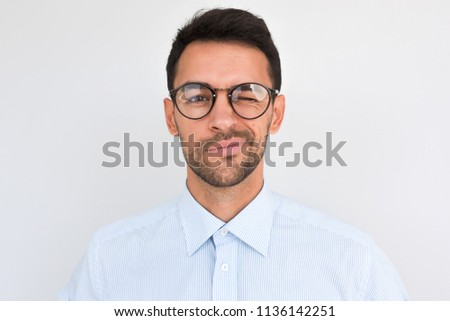 Portrait of unshaven handsome male frowns, being dissatisfied with something, blink with eye, wears round glasses and blue shirt, isolated over white studio background. People and emotion concept.