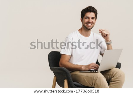 Portrait of unshaven laughing man working with laptop while sitting on armchair isolated over white background