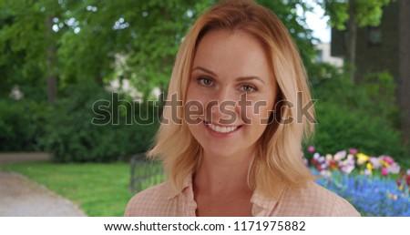 Portrait of upbeat Caucasian female looking happily at camera in public park