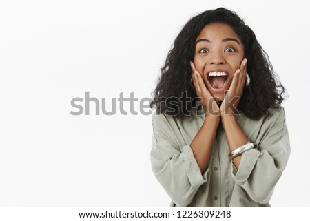 Portrait of upbeat enthusiastic and delighted surprised dark-skinned girlfriend with curly hairstyle yelling from amazement and joy receiving awesome surprise touching cheeks from happiness.