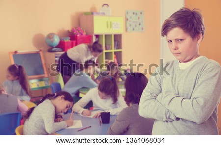 Portrait of upset angry boy in schoolroom on background with pupils studying with teacher #1364068034