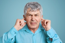 Portrait of upset annoyed mature man plugs ears with fingers, dressed in formal shirt, poses against blue background, doesn`t want to hear anything. Irritated elederly man ignores someone