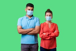 Portrait of upset couple with surgical medical mask standing together with crossed hands, looking sideways at each other with resentful glance, suspicion. isolated on green background, indoor studio