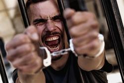 Portrait of upset handcuffed man imprisoned for crime, punished for serious villainy. Arrest, gangster, pain concept.