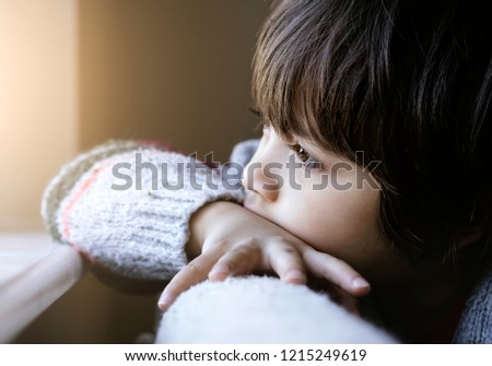 Portrait of upset little boy sitting alone,Kid sad face looking out of window,Unhappy child wearing knit jumper looking out with thinking face, Spoiled children concept  #1215249619