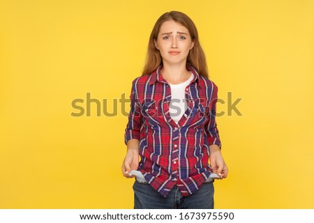 Portrait of upset poor ginger girl in shirt showing empty pockets and looking frustrated about loans and debts, has no money, jobless going bankrupt. indoor studio shot isolated on yellow background Foto stock ©