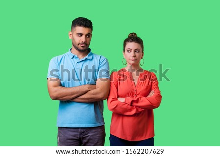 Portrait of upset young couple in casual wear standing together with crossed hands, looking sideways at each other with resentful glance, suspicion. isolated on green background, indoor studio shot