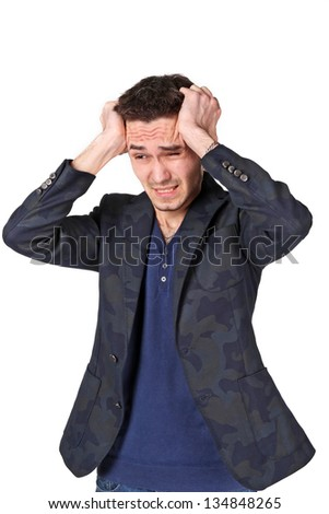 Portrait of  upset young man grabbing his head in desperation over white background
