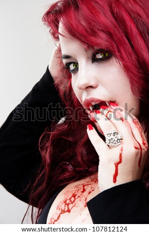 Portrait of vampire bloody woman with yellow cat eyes