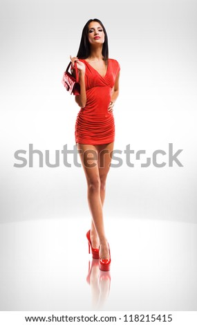 Portrait of very fashionable slender brunette beauty in red hot little dress.