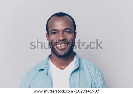 Portrait of virile, harsh, trendy, cheerful, glad man with beaming smile isolated on grey background