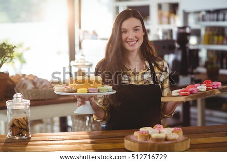 Portrait of waitress standing at counter with desserts in cafe #512716729