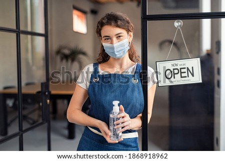 Portrait of waitress wearing face mask and holding a bottle of sanitiser at cafe entrance during covid-19 pandemic. Small business owner holding sanitizer reopening after coronavirus lockdown.
