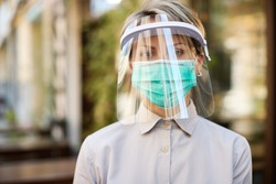Portrait of waitress wearing visor and protective face mask while working at cafe during virus epidemic.