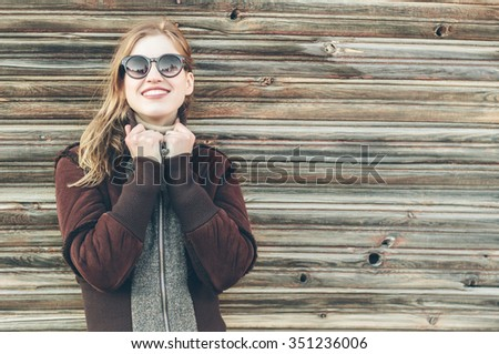Stock Photo Portrait of warm Young smiling Hipster Woman against Wooden Wall Background. Autumn or winter Urban Concept of a beautiful blond girl with teeth smile in sunglasses.