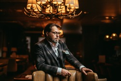Portrait of wealthy prosperious handsome businessman, dressed in tailored three-piece suit sitting in leather arm-chai at elite gentlemen club with lighted multi-lamp chandelier behind.