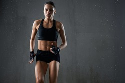Portrait of wet female bodybuilder with perfect muscular body jogging on spot isolated in empty hall, loft interior. Concentrated athletic woman practicing hard cardio sport exercise under rain.