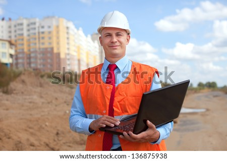 Portrait of white-collar worker wearing protective helmet works on the building site
