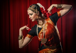 Portrait of white girl as an Indian classical dancer in traditional dress and performing dance performance on the red curtain background. Classical indian temple dance form Bharatanatyam. Dance pose