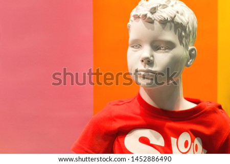 Portrait of white mannequin baby boy in red t-shirt on bright colorful background. Little doll in shop window. Boutique with young mannequin. Children's clothing department. Face closeup