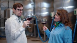 Portrait of wine makers with wine glass at manufacture with metal tanks. Male and female sommelier tasting red wine in glasses standing near metal tanks for wine fermentation