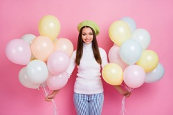 Portrait of winsome cheerful girl holding in hands bunch air celebratory balls isolated over pink pastel color background