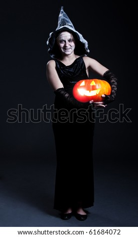 portrait of witch in hat with orange pumpkin. halloween theme
